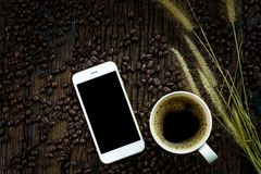 Smartphone with black blank screen, coffee cup, dry grass flowers and roasted coffee beans on wooden texture background Stock Image