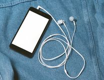 Smartphone with black case and a blank white screen and plugged in headphones ear buds on the background of denim. Smartphone with black case and a blank white stock photos