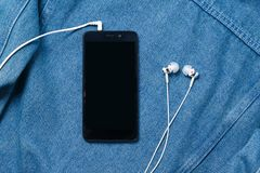 Smartphone with black case and a blank white screen and plugged in headphones ear buds on the background of denim. Smartphone with black case and a blank white stock photography