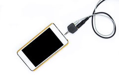 Smartphone with black and white jack plug on background Royalty Free Stock Photography