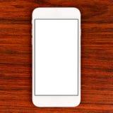 Smartphone blanc élégant au-dessus de table Photographie stock libre de droits
