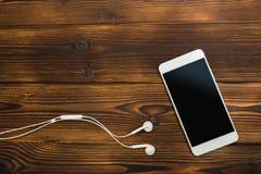 Smartphone blanc avec des écouteurs sur le fond en bois photographie stock libre de droits