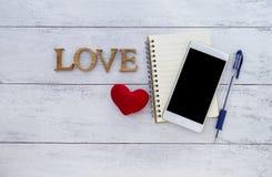 Smartphone blanc et amour en bois Photographie stock libre de droits