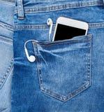 smartphone blanco con los auriculares en el bolsillo trasero de tejanos fotografía de archivo libre de regalías