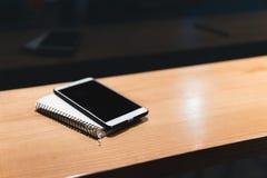 Smartphone blanco, cuaderno tabla de madera en el café, trabajos del Freelancer remotamente M?rketing en l?nea, educaci?n para el imagen de archivo