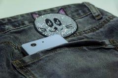 Smartphone blanco en los vaqueros grises del bolsillo trasero con el appliqué de strasses foto de archivo