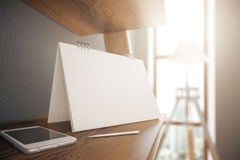 Smartphone and blank calendar. Closeup of blank calendar stand, smartphone and pen placed on wooden desktop in interior with daylight. Mock up, 3D Rendering Stock Image