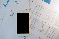 Smartphone with blank screen on background of financial reports royalty free stock images