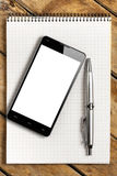 Smartphone Blank Screen Note Pad with Pen. Smartphone with blank white screen and silver pen on a white spiral squared notebook on rustic wooden table viewed Stock Photography