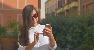 Smartphone bonito novo do uso da mulher na cidade europeia vídeos de arquivo