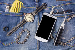 Smartphone, bracelet, portable battery and watch on jeans backgr Stock Images
