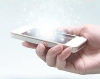 Smartphone branco com a mão isolada no fundo claro Imagem de Stock Royalty Free