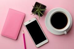 Smartphone branco e uma xícara de café e um bloco de notas cor-de-rosa em um fundo cor-de-rosa brilhante Vista de acima fotos de stock