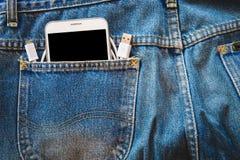 Smartphone branco em sua calças de ganga do bolso com cabo de USB para dados ou informação de transferência no fundo isolado Imagem de Stock Royalty Free