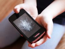 Smartphone with a broken display in children`s hands, object royalty free stock photo