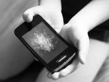 Smartphone with a broken display in children`s hands, object stock image