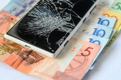 Smartphone with broken display lying on money banknotes on a White background. Stock Photography