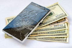 Smartphone with broken display lying on money banknotes Stock Photos