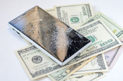 Smartphone with broken display lying on money banknotes Royalty Free Stock Photography