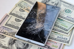 Smartphone with broken display on money background Royalty Free Stock Images