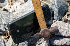Smartphone broken glass with hammer on gravel stones. Selective focus.  stock image