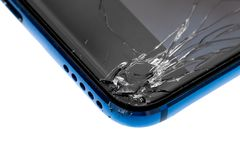 A smartphone with broken glass screen close-up. A smartphone with broken glass screen close-up of the angle of the phone isolated on a white background royalty free stock photography