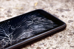 Smartphone with broken screen. Black smartphone with broken screen on the ground royalty free stock photography