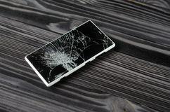 Smartphone with broken screen on dark background royalty free stock photos