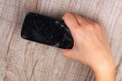 Smartphone with a broken screen in the girl`s hand. A smartphone with a broken screen in the girl`s hand on a wooden table. Close-up. Studio lighting stock photos