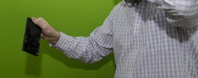 Smartphone with broken screen with green background. Hand holding a smartphone with broken screen stock photography