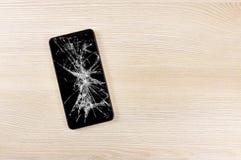 Smartphone with broken screen. Modern mobile phone with broken screen on wooden background and copy space stock photos
