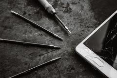 Smartphone with a broken screen and repair tools. Smartphone with a broken screen and repair tools on the dark background. Close-up stock photos