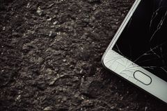 Smartphone with a broken screen. Smart phone with broken screen on dark background. Close-up royalty free stock image