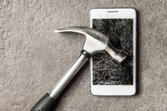 Smartphone with broken screen. And a hammer stock photography