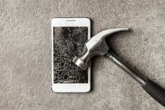 Smartphone with broken screen. And a hammer stock images