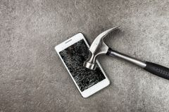Smartphone with broken screen. And a hammer stock photo