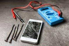 Smartphone with broken screen. And multimeter stock photo