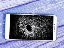 Smartphone with a broken screen on a wooden background.  royalty free stock photos