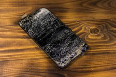 Smartphone with broken screen on wooden background. Smartphone with broken screen on the wooden background stock images