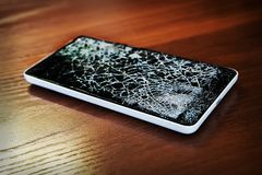 Smartphone with broken screen on the wooden table. Modern frameless Smartphone with broken screen on the wooden table stock images