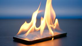 Smartphone is burning on a table on a blue background royalty free stock photo