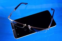 Smartphone for business, entertainment, glasses with diopters for reading. Smartphone is a pocket PC with Mobile applications. Glasses with diopters for vision stock photo