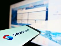 Smartphone with business logo of Swiss telecommunications company Swisscom AG on screen in front of website.