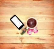 Smartphone, cadeaux et une tasse de thé sur le fond en bois Photographie stock libre de droits