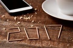 Smartphone, café e número 2017, como o ano novo Fotografia de Stock