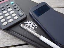 Smartphone, calculadora, orden del día, pluma de la aguja y paperclips Fotos de archivo libres de regalías