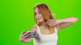 On the smartphone camera redhead girl doing selfie. Green screen stock video