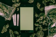Smartphone and Cannabis Marijuana buds in the package on the table and joint on table in a moody green tone horizontal. Smartphone and Marijuana Cannabis buds in royalty free stock photography