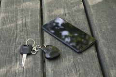 Smartphone and car keys lie on a wooden table stock photos
