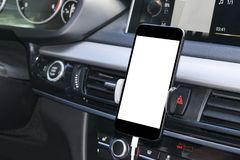 Smartphone in a car use for Navigate or GPS. Driving a car with Smartphone in holder. Mobile phone with white screen. royalty free stock image